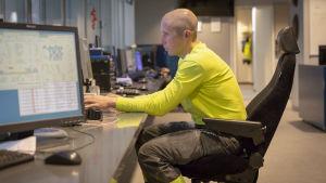 Ett kontrollrum. På en stol sitter en man med rakad skalle vid en dator.
