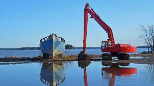 En båt och en grävmaskin står vid stranden under vintern.