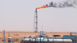 Saudiarabialainen öljykenttä. Poraustornista nousee liekkejä.