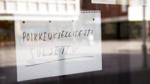 Poikkeuksellisesti suljettu-lappu ravintolan ikkunassa Helsingin Tallinnanaukiolla.