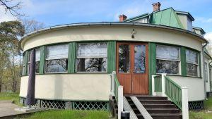 En vit byggnad med gröna fönsterkarmar.