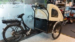 Svart elcykel med tre hjul och en vagn framtill.
