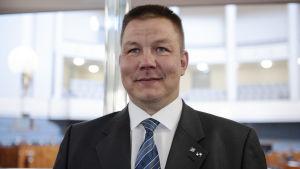 Juha Mäenpää fotograferad rakt framifrån. Han ler.