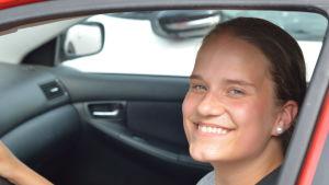 Ung tjej sitter i en bil och ler mot kameran.