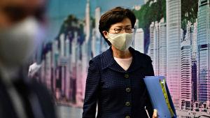 Kvinna i ansiktsskydd med mapp i handen.