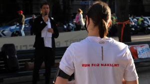 """En kvinna som bär en tröja med texten """"Run for Navalny"""" på ryggen"""
