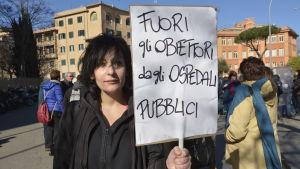 Demonstrant med skylt på italienska i Rom där det står: Ut med samvetsvägrarna från de offentliga sjukhusen