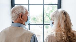 Äldre par med munskydd ser ut genom fönstret.