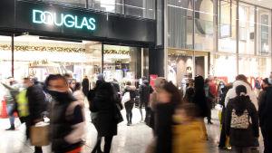 En livlig shoppinggata. I bakgrunden ses butiker med ljusa skyltfönster. I förgrunden människor som hastar förbi kameran, de flesta är suddiga och går inte att identifiera.