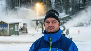 Niklas Blomander står framför en snökanon och en slalombacke