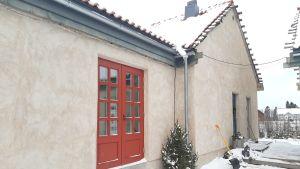 Grått hus med röd dörr.