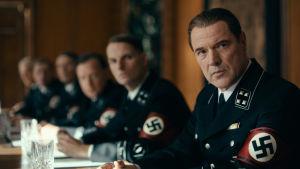 Etualalla Carl Seeband (Sebastian Koch) istuu kokouspöydän ääressä SS-upseerin univormussa. Taustalla muita SS-miehiä.