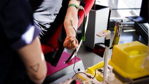 En person som ger blod i Sanoma-husets blodtjänst.