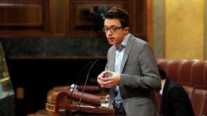 En man i grå kostym står i en talarstol.