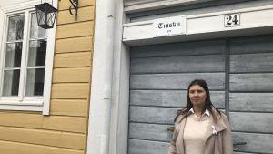 Niina Nyblom står framför träporten till sitt gamla hus i Nådendal