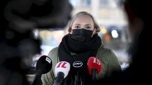 Inrikesminister Maria Ohisalo i svart munskydd och ytterkläder. Hon talar till reportrar vid Ständerhusets trappa i Helsingfors. Framför henne syns Yles, Iltalehtis, MTV:s och Ilta-Sanomats mikrofoner.