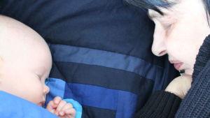 Iidan äiti nukkuu lapsenlapsensa vierellä. Hänellä on siniset hiukset ja musta villapaita.