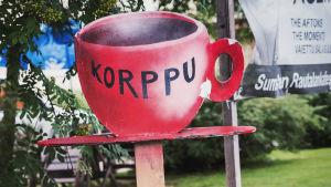 """Skylt formad som en röd kaffepanna med texten """"Korppu""""."""