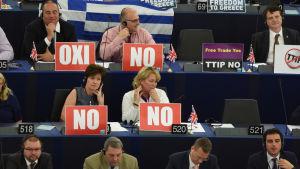 Parlamentariker demonstrerar genom att visa Oxi-skyltar i Europaparlamnetet