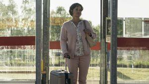 Britt-Marie står i en busskur på vilken det står Borg.