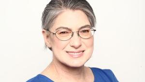 Leende kvinna i blå blus med glasögon.