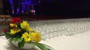 Ett bord med blommor och glas. Frida Andersson i bakgrunden.