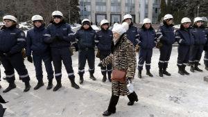 Kvinna passerar kravallpolis i Moldaviens huvudstad Chișinău 24 januari 2016