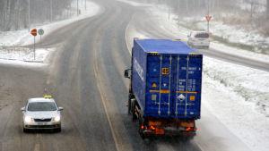 En taxi, en lastbil och en personbil kör på en slaskig riksväg. Snön yr.