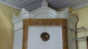En vit kakelugn med gulddekor och mycket krusiduller.