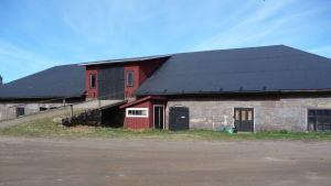 En ladugård i gråsten med stort svart tak. Finns på Rilax gård i Bromarv