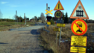 Trafikmärkena är många vid plankorsningen vid Gislomvägen.