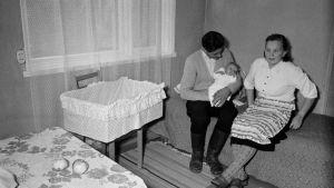 Mamma, pappa som håller i barnet i ett sparsamt möblerat rum på 50-talet kanske.