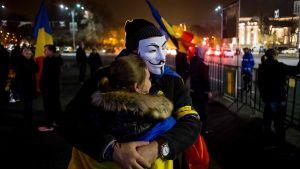 Två unga demonstranter utanför regeringsbyggnaden i Bukarest under en tidigare protest den 19 november.