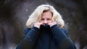 Paula Noronen kurkkaa takin sisältä lumisateessa.