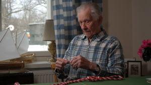 Otto Sjödahl håller ett miniayrfisknät i handen, bakom sig har han båtminiatyrer