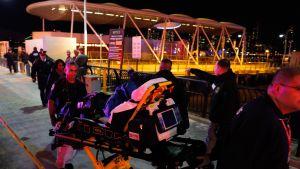 En av passagerarna i olyckshelikoptern tas om hand av ambulanspersonal.