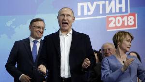 Putin reagerade glatt på nyheten om sitt omval som han hörde då han befann sig bland sina anhängare och kampanjmedarbetare