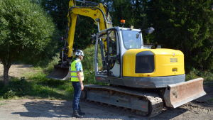 En grävmaskin gräver ner markkabel i Saxby