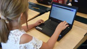 En flicka sitter vid en dator