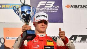 Mick Schumacher håller upp segerpokalen