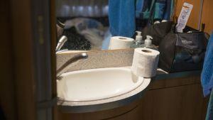 Asuntovaunun sängyn vieressä on pieni lavuaari ja peili.