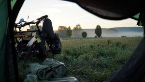 En bild tagen inifrån ett tält. Vi ser ut genom tältöppningen och kan skymta två cyklar. Tältet finns en på en äng med högt gräs. I horisonten syns dimma.