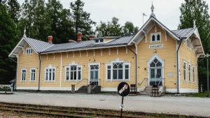 Vanha, keltaiseksi maalattu asemarakennus, jonka editse kulkee rautatiekiskot.