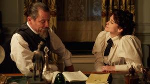 Willy och Colette lutar sig över en text på ett skrivbord.