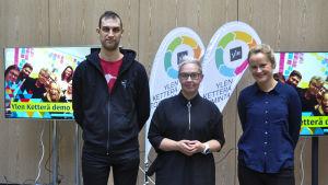 Kolme ihmistä seisomassa rivissä