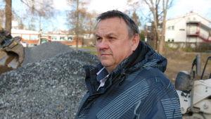 En medelålders man med kort mörkt hår står intill en grushög.