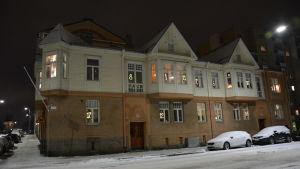 Julkalendersbelysning i fönstren på ett trä- och stenhus en vinterkväll med snö på gatan.