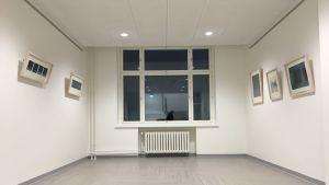 Ett fönster och vita väggar med tavlor.