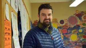 Simon Store står iklädd blå jacka i ett klassrum.