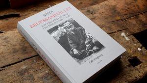 Ole högbergs bok Sista brukssamhället ligger på en brun hyvelbänk. En svartvit bild på en smutsig pojke i basker på omslaget.